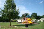 Playground Structure, Trash Can, and Shade Tree Compose the Park